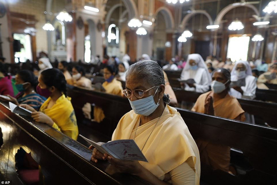 INDIA: A woman reads an order of service at St. Joseph's Cathedral in Prayagraj on Good Friday