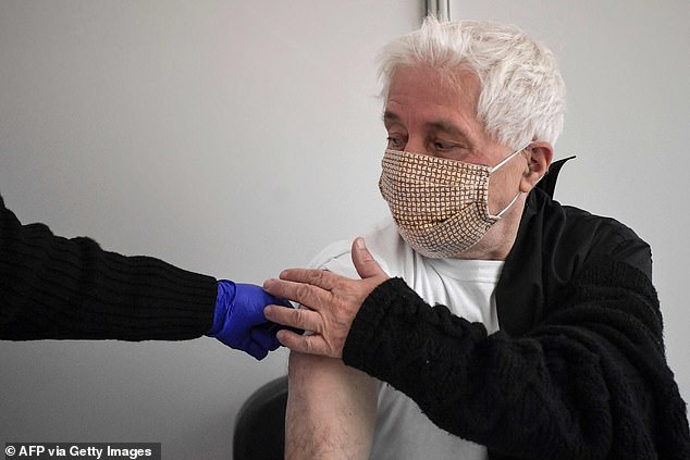 A study published by the organisation, full name Centers for Disease Control and Prevention, this week found that Pfizer and Moderna's vaccines appear to prevent 90 per cent of all infections, including those without any symptoms, which experts said raises hopes they will stop most transmission - but not all of it and not for definite. (Pictured: A man is vaccinated with the Moderna jab in Athens, Greece, today)