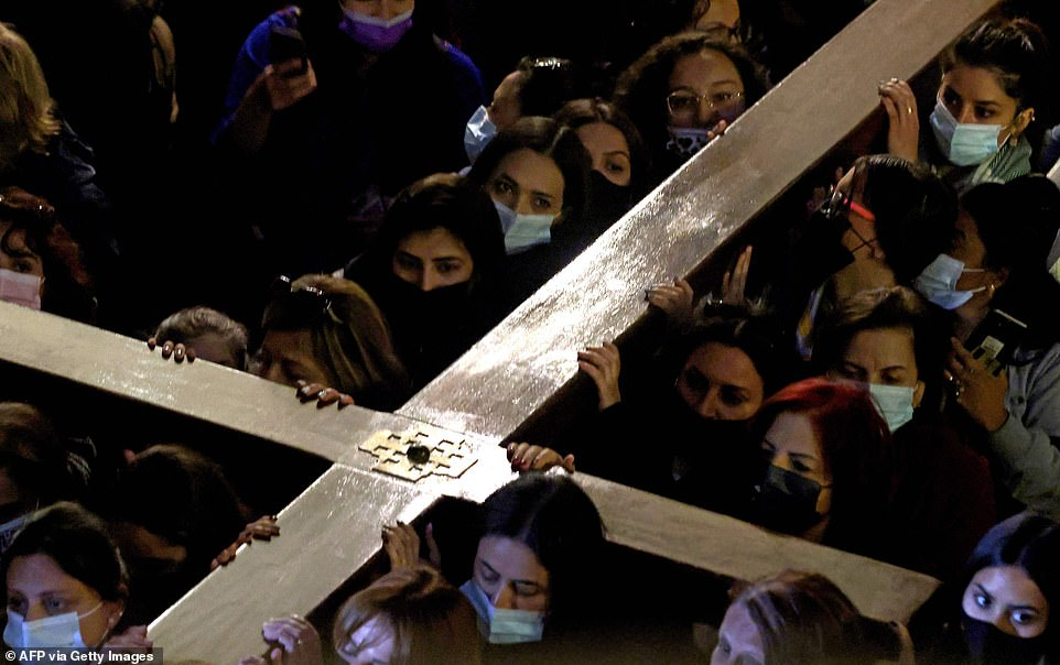 ISRAEL: Women are seen wearing masks as they carry a wooden cross through the Church of the Holy Sepulchre, which is built on the site where Jesus was crucified