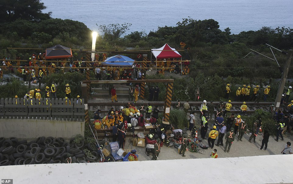 Rescue workers gather near the site of a derailed train near the Toroko Gorge area in Hualien, Taiwan