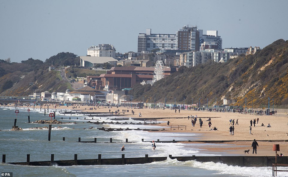 People enjoy the warm weather on Boscombe beach in Dorset, with the hot weather which baked much of the UK this week set to give way to a chilly Easter weekend