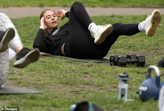 Natural beauty:The reality star appeared to go make-up free as she dropped to the floor to work on her washboard abs
