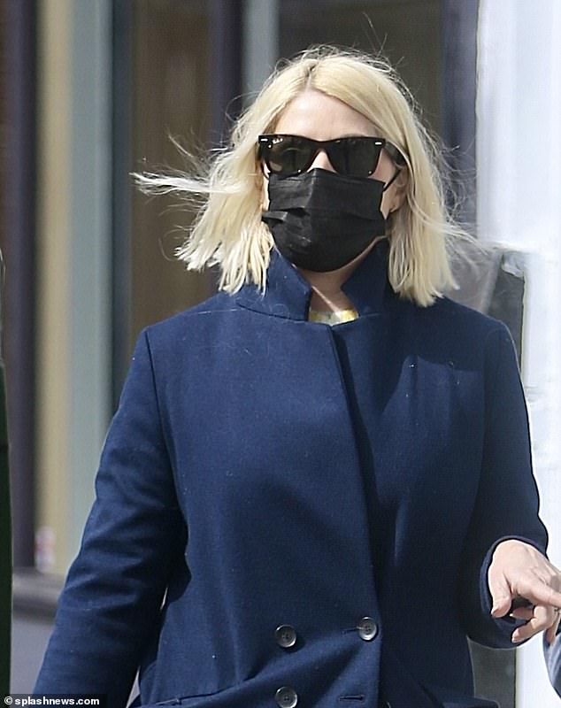 Casual look: The This Morning presenter looked effortlessly chic as she strolled down a London high street, teaming her coat with a black face mask and a crisp pair of white trainers