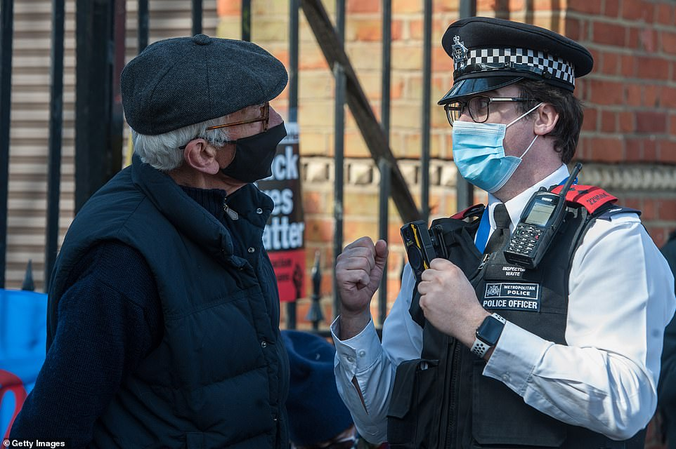 A police officer speaks to a person they perceive to be an organiser of the protest during the rally in Finsbury Park, London