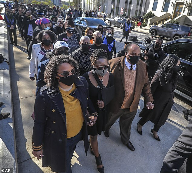 From left foreground, Toni Watkins; her partner, state Rep. Park Cannon; Martin Luther King III, and his wife, Andrea King, march silently with others along Mitchell Street in front of the Capitol building in Atlanta. Cannon returned to the Statehouse on Monday, March 29, 2021 for the first time since she was arrested after knocking on Governor Brian Kemp's private office while he was delivering remarks about the state's new elections restrictions