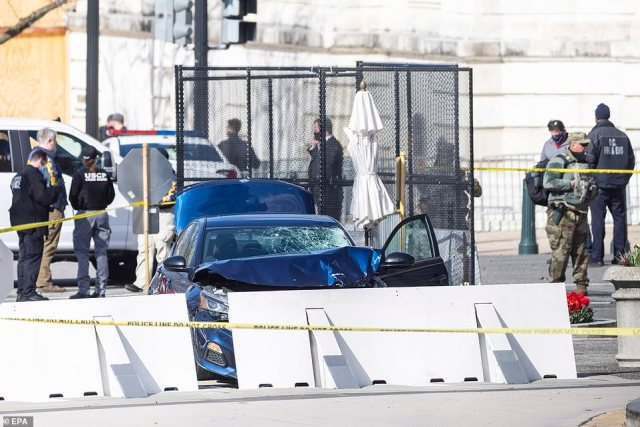 The car is seen smashed into a barrier. Here the suspect had gotten out of the vehicle wielding a knife before being shot dead
