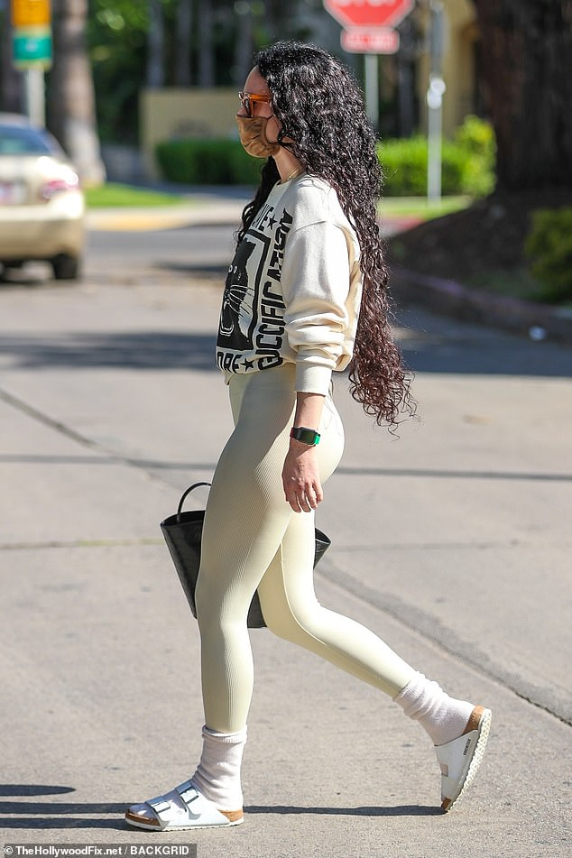 Natural beauty: She highlighted her peachy posterior in her cream leggings and appeared to go make-up free for the outing
