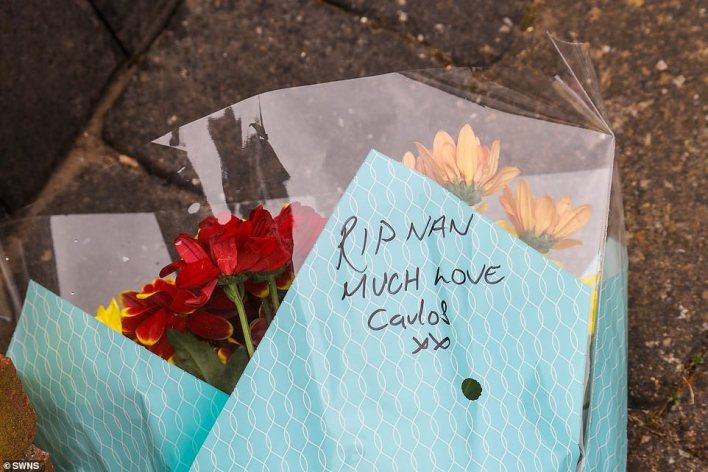 Floral tributes, including one reading 'RIP Nan, much love, Carlos' have been left outside the elderly woman's home today