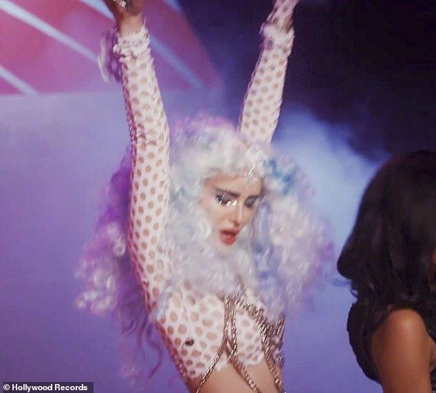 Hitting the dance floor: She also evoked the 1980s when she put on a voluminous bushy white wig and modeled a fishnet crop top that had chains dangling from it
