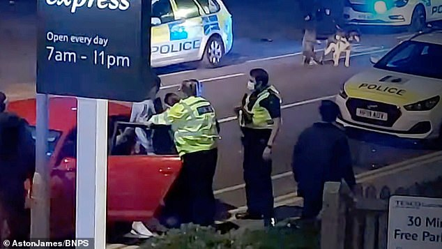 Police officers stop one of the revellers by a car outside a Tesco Express where fights erupted at around 9.30pm
