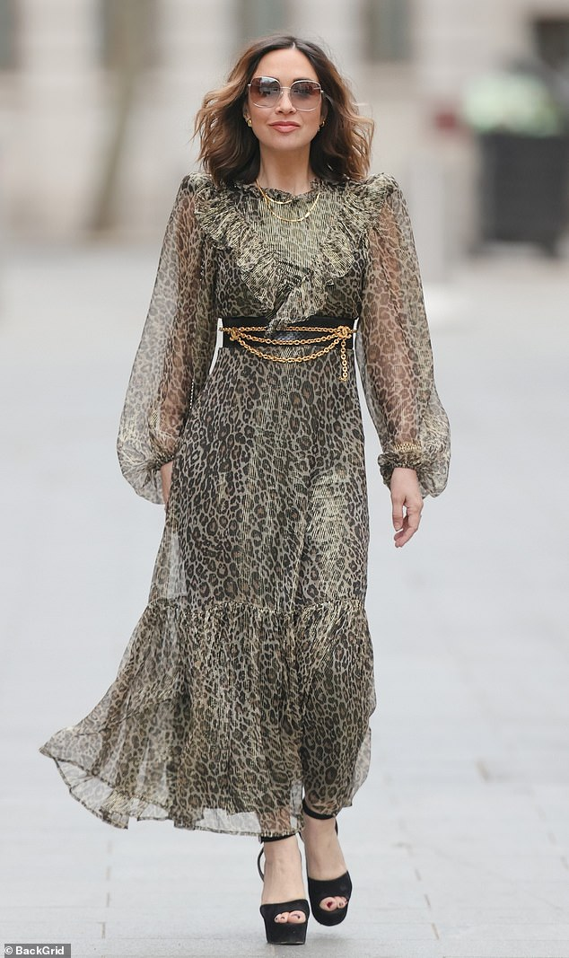 Gorgeous:Her sheer animal print long sleeved dress was paired with a black leather and gold chain belt which cinched in her waist
