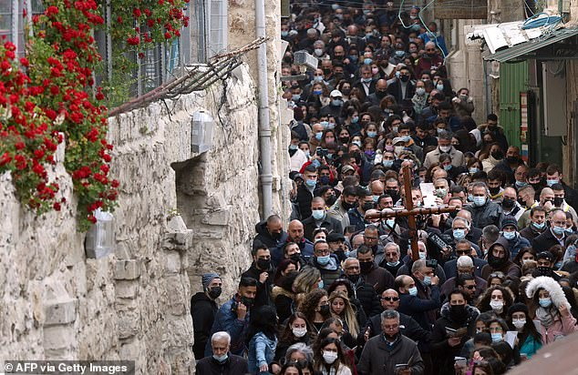 Christians walk down the Via Dolorosa (Way of Suffering) in Jerusalem after restrictions were eased following the tremendous success of the country's vaccine roll-out