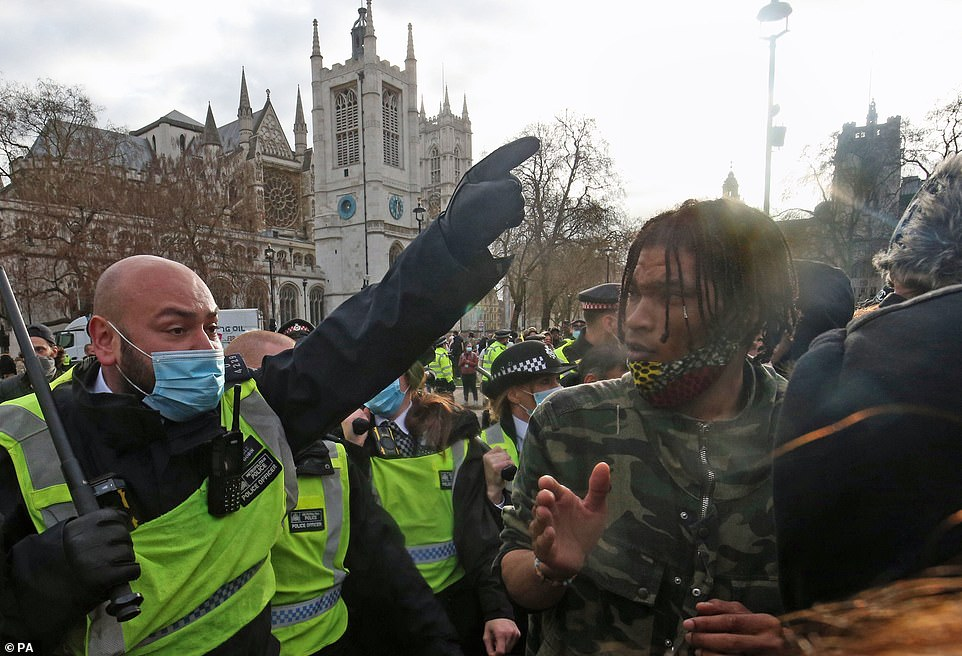 A policeman holding a baton faces demonstrators during a 'Kill the Bill' protest against the Police, Crime, Sentencing and Courts Bill in Parliament Square, London