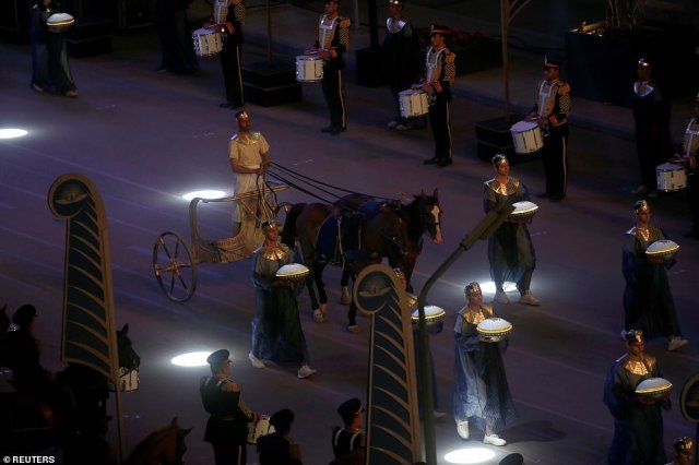 An artist is pictured in a chariot while performing during the parade. Guards on horses and Egyptian celebrities and signers followed the motorcade