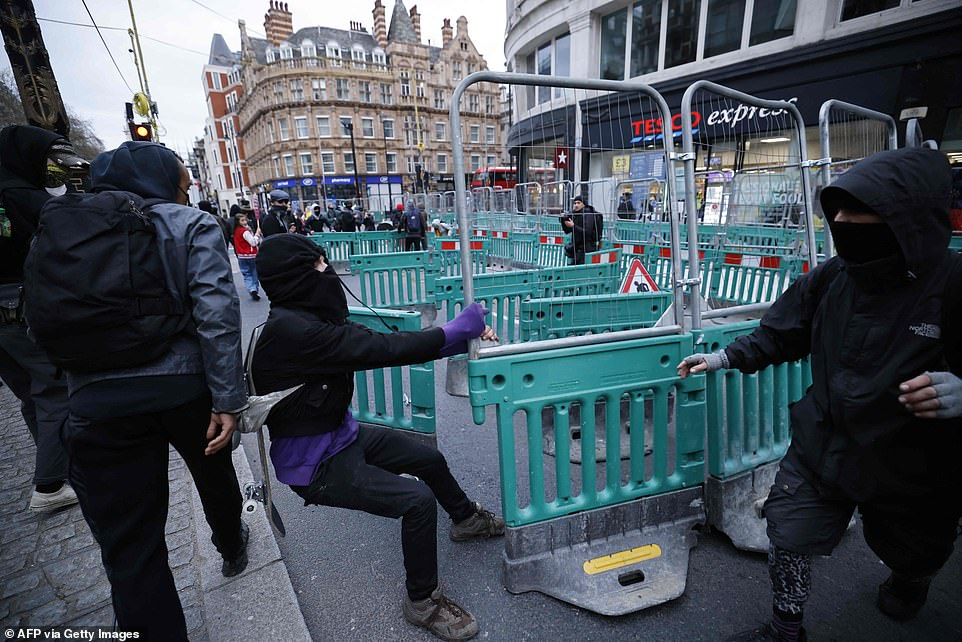 Demonstrators use street barriers to block a road during a 'Kill the Bill protest in central London on Saturday