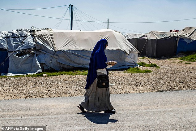 At least three more British jihadi brides are staying in the same Syrian refugee camp as Shamima Begum – and each of them is trying to return to the UK. Pictured: A woman walks throughCamp Roj in Syria