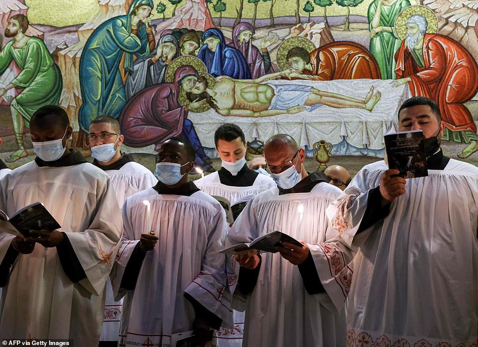 Fransiscan friars pray during a mass on Easter Sunday while wearing face masks at the Church of the Holy Sepulchre in Jerusalem