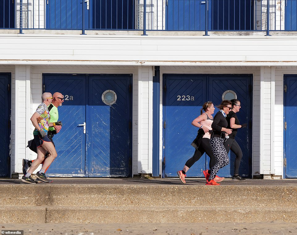 Runners burn off their easter chocolate on a jog along the seafront in Sandbanks, Dorset, Easter Sunday