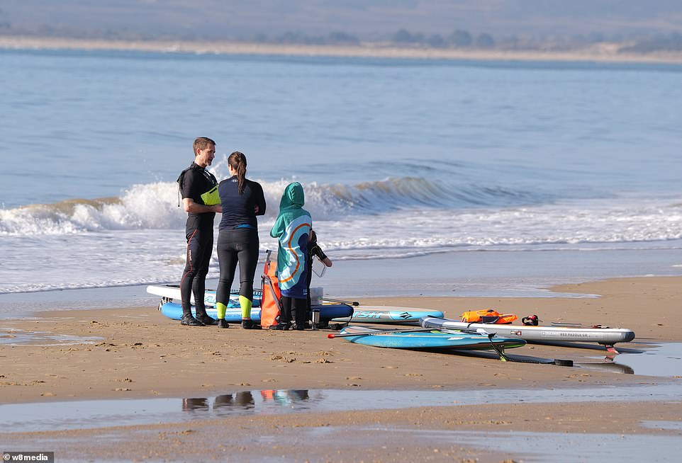 A young family get ready to go paddle boarding in Sandbanks this morning, with the whole family involved