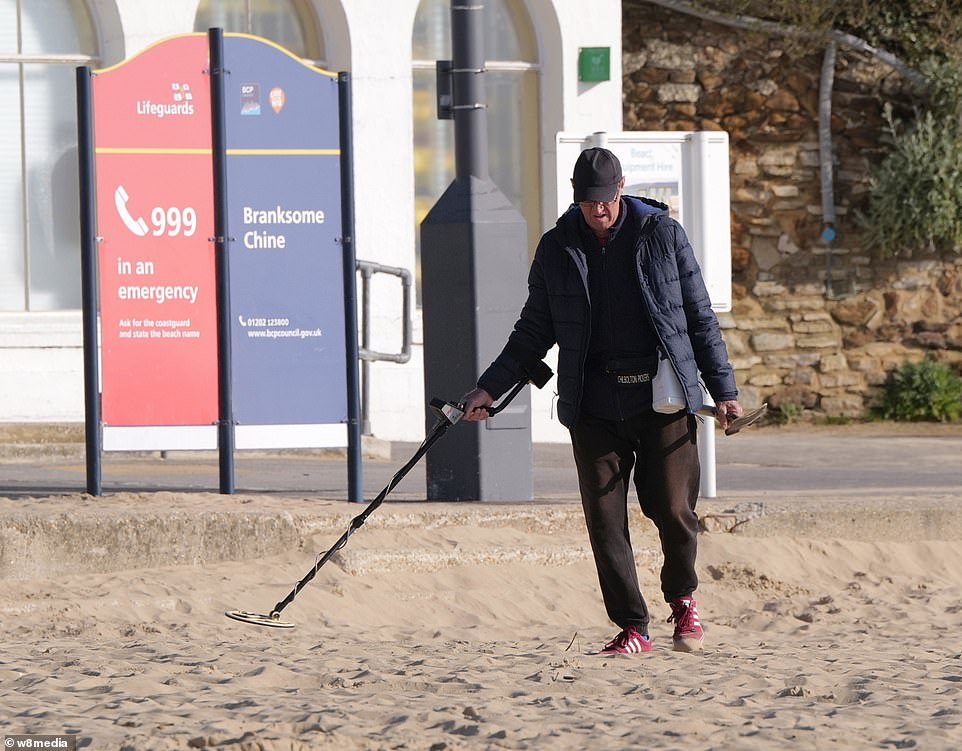A man uses a metal detector on Sandbanks in Dorset in the hopes of finding lockdown treasure on Easter Sunday