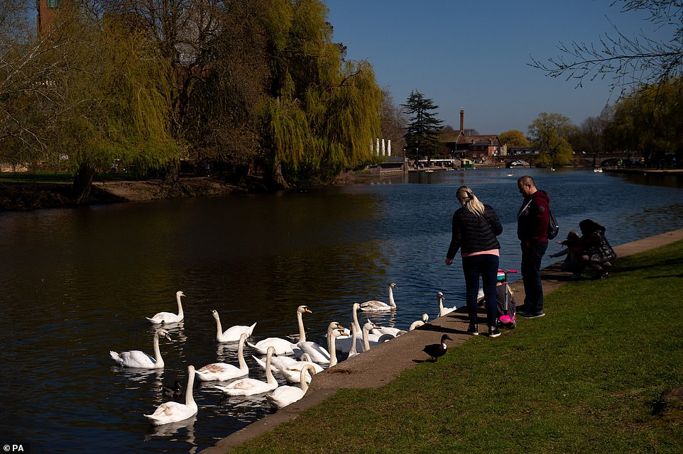 A family feed swans and ducks in Stratford-upon-Avon in Warwickshire, Easter Sunday