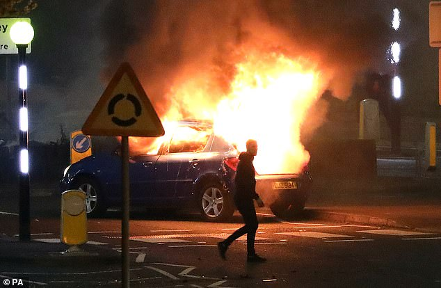 A man walks past a burning car after it was hijacked at the Cloughfern roundabout in Newtownabbey and set alight