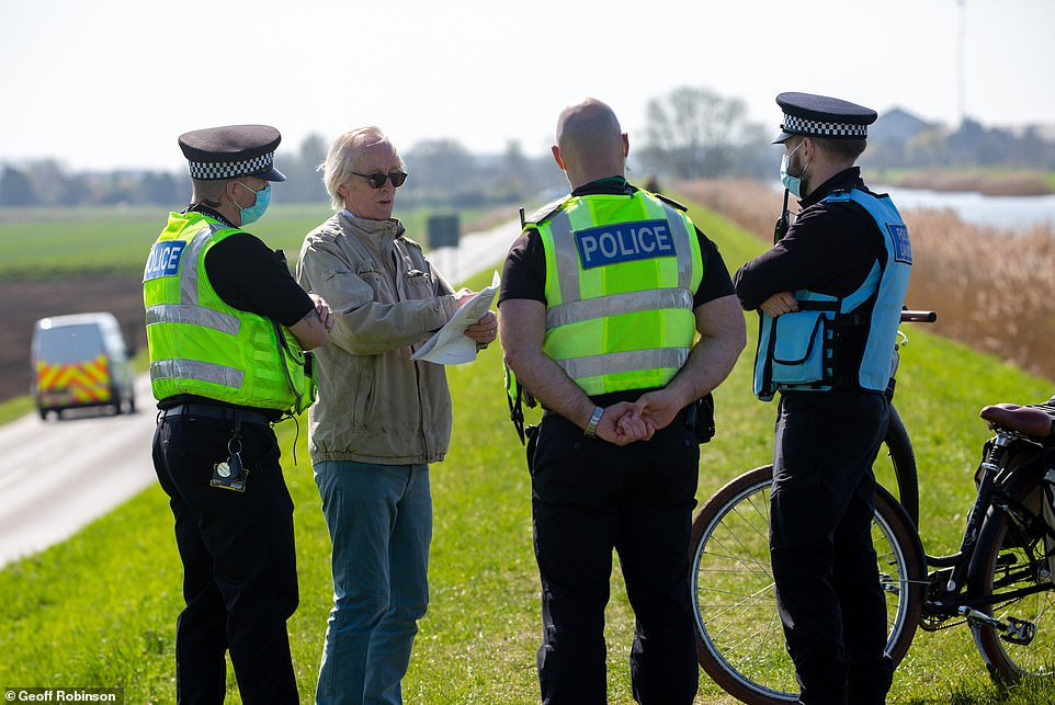 A man is questioned by police as he tries to go down the footpath by the River Great Ouse where the Boat Race will be held, between Ely and Littleport in Cambridgeshire