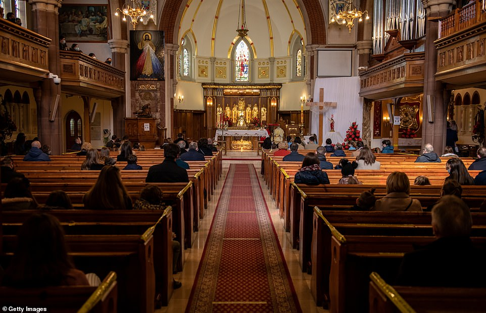 Christians sit apart socially distanced during an Easter Sunday service at Christ the King church this morning