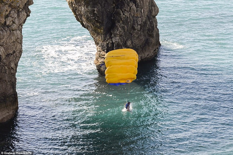 One of the base jumpers with a yellow parachute leaps off the limestone arch and into the sea while his mate waits at the top