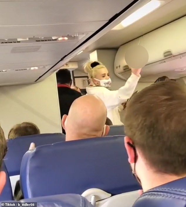 The woman is then seen throwing up her middle finger to the rest of travelers