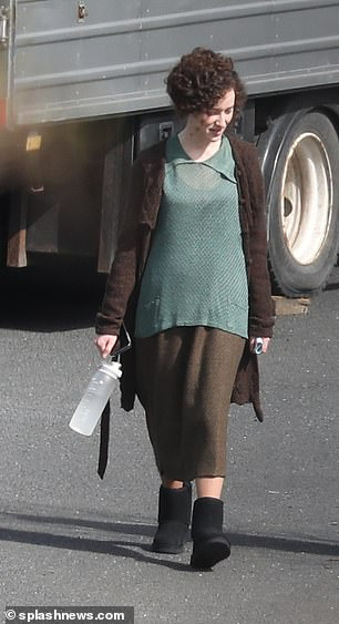 Period drama: She was seen in a teal blouse and brown skirt, adding black boots to the look