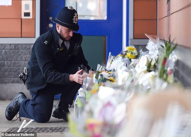 A police officer lays flowers outside Croydon Custody Centre following the death of Sergeant Ratana