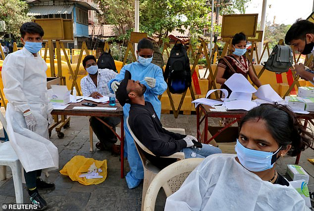 The variant was linked to between 15% and 20% of samples sequenced from India's Maharashtra state, which has seen a 50% spike in cases in the last week. Pictured: A healthcare worker tests a man for COVID-19 in Mumbai, India, April 5