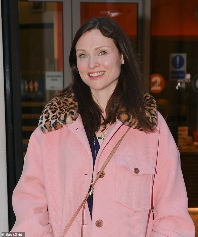 Casual smile: The Murder on the Dancefloor hitmaker, 41,flashed a warm smile to onlookers as she departed the London studios before donning a frilly, floral face-mask