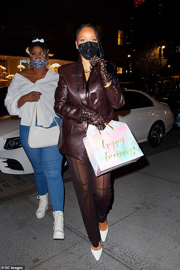 Party guest:Rihanna carried a colorful gift bag displaying the words happy birthday, and was also seen with a small Fendi tote bag hanging from her arm
