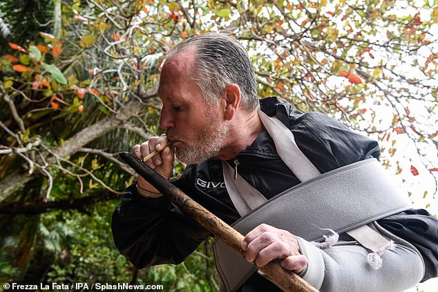 Lighting up: Gazza was also using a burnt piece of wood to light a cigarette