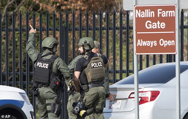 Members of the Frederick Police Department Special Response Team prepare to enter Fort Detrick at the Nallin Farm Gate in a convoy of vans and sedans following a shooting in Riverside Tech Park