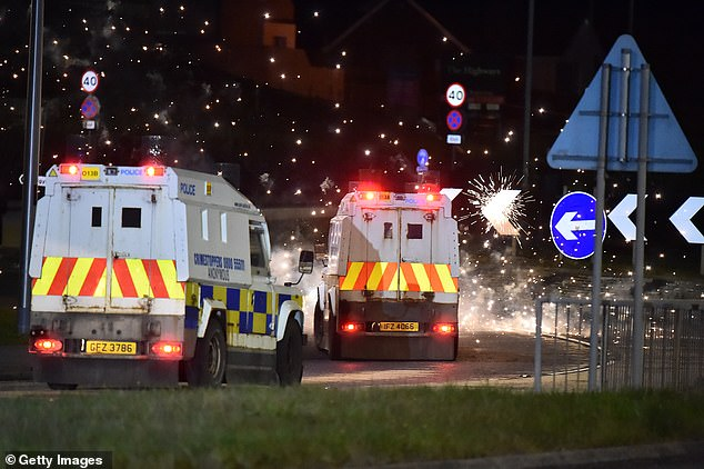 Police come under attack from fireworks and rocks as they unblock the main route into Larne town and harbour as Loyalists hold an anti Northern Ireland Protocol protest on Tueaday