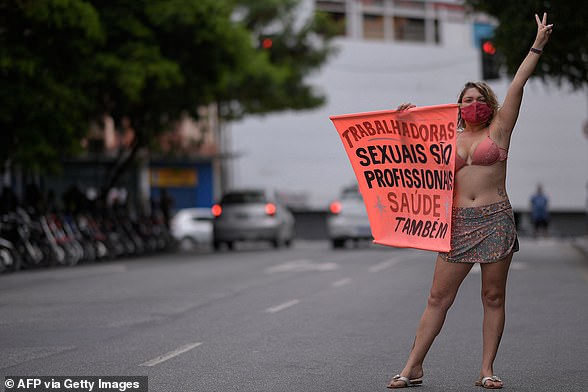 The Brazilian government has prioritised health workers, teachers, the elderly, indigenous people and people with underlying health conditions for the first round of vaccinations. Pictured: A sex worker holds a sign saying: 'Sex workers are health professionals too' during a protest
