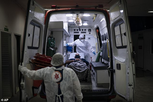 Paramedics transport a Covid patient to a hospital inRio de Janeiro on Tuesday.Brazil's health system is buckling under the strain of the latest virus wave, which has forced doctors into agonising decisions over which patients to give life-saving care and led cemeteries to hold nighttime burials to deal with the crush of coffins.