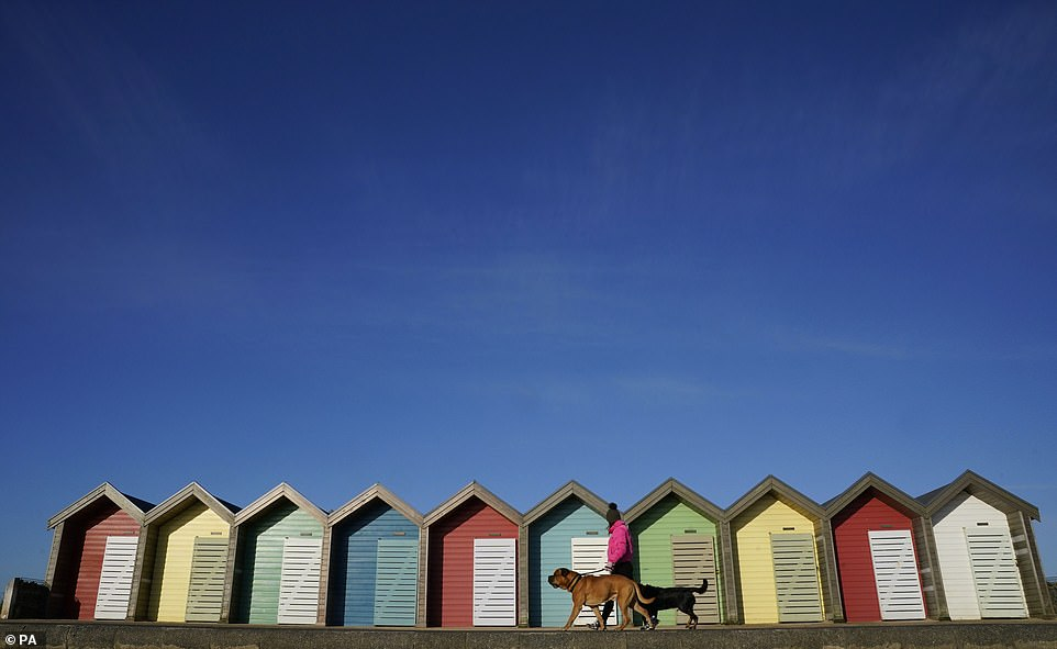 A woman walks her dog past beach huts at Blyth beach in Northumberland in the cold this morning