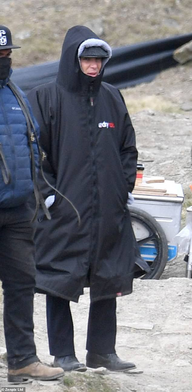 Bundled up:Cillian, who plays gang leader Tommy Shelby, sported his character's signature flat cap beneath his hood and black gloves as he joined his fellow cast and crew on location