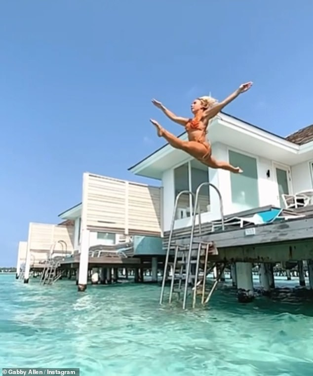 Flying high:On Wednesday Gabby demonstrated her impressive flexibility as she did the splits in mid-air before falling into the turquoise sea at her holiday villa