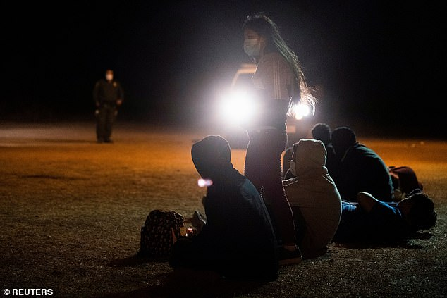 A group of unaccompanied children await to be transported to a processing facility after they safely made it into the United States by crossing over from Mexico through the Rio Grande on Tuesday