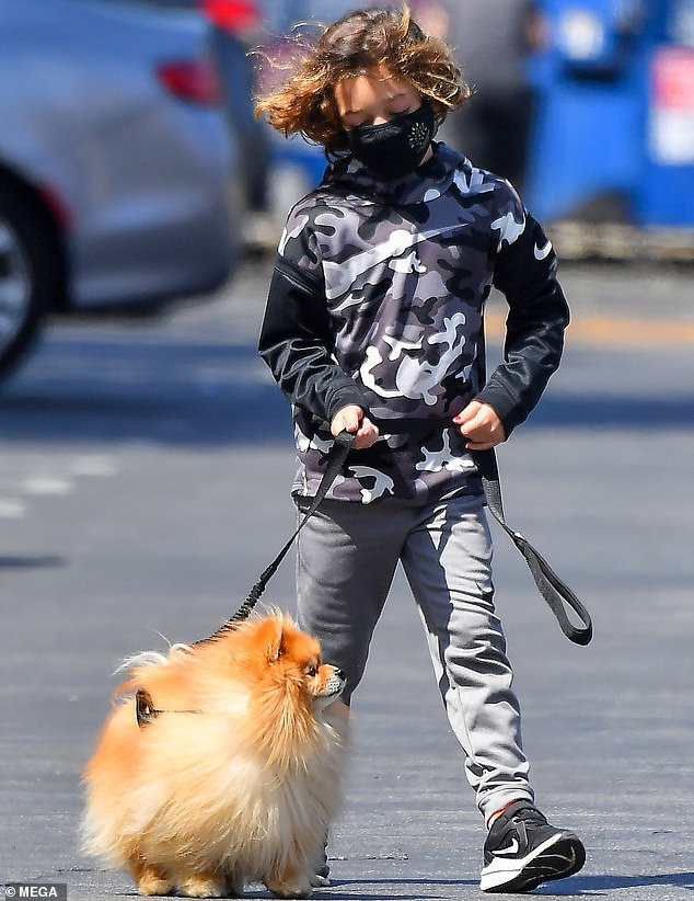 Out and about: While heading across the parking lot this Wednesday the father-son duo were also seen walking Gavin's beloved Pomeranian Chewy