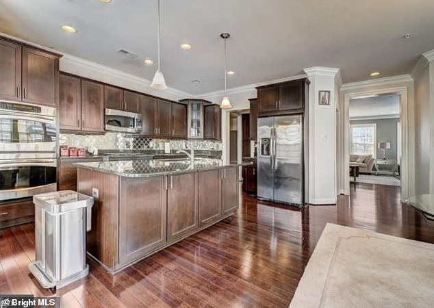 The home's kitchen includes amenities such as an island and stainless steel appliances