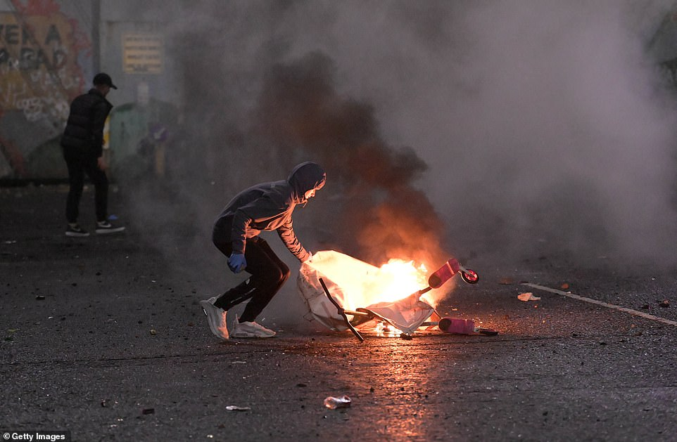 : A person approaches a fire during clashes at the Springfield Road/Lanark Way interface