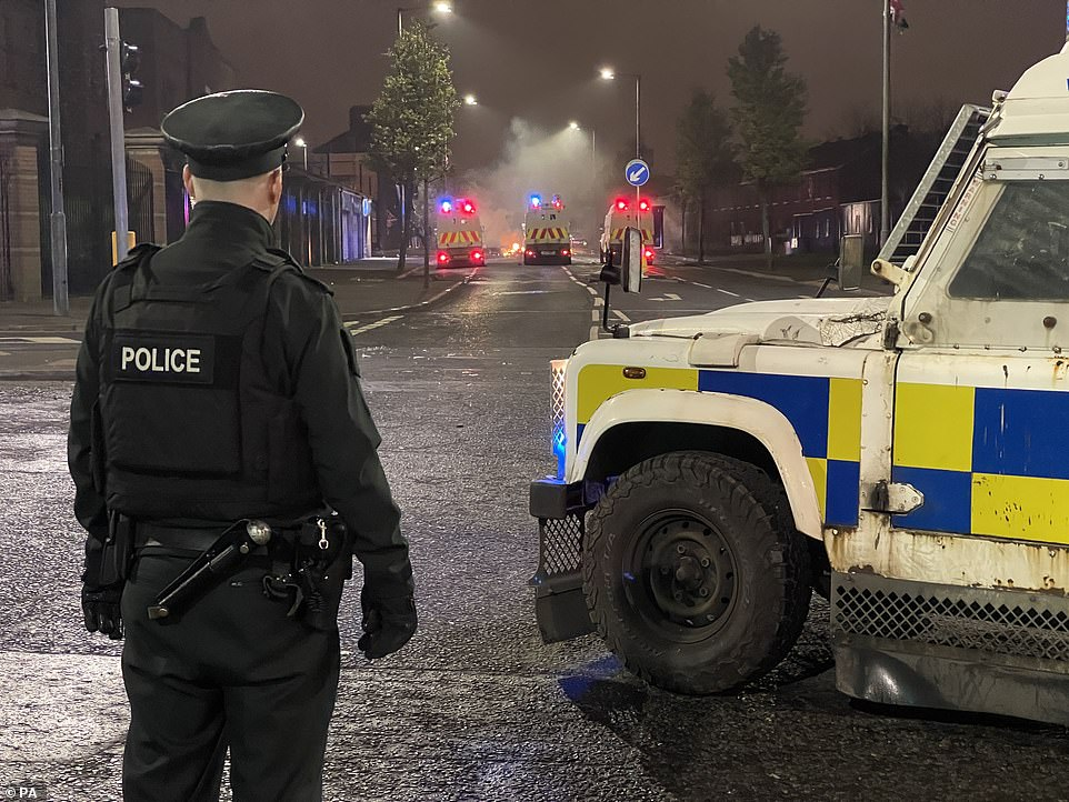 APSNI officer stands on North Queen Street in Belfast looking towards Tigers Bay where three Police Land Rovers form a police line during further unrest