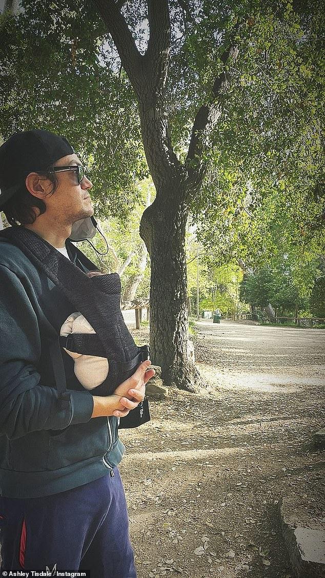 Imagen perfecta: en su Instagram durante su salida al parque, Ashley tomó una dulce foto de Christopher cargando a Júpiter en su mochila porta bebé mientras el sol brillaba a través de los árboles.