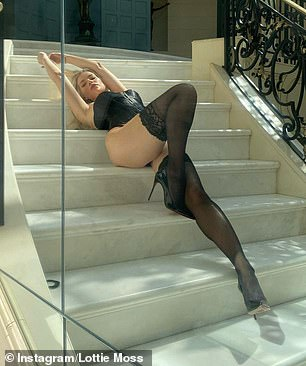 Recline: Posing on a staircase at a lavish mansion, the beauty displayed her enviable legs in black stockings and patent stiletto heels
